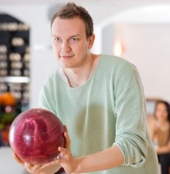 Young man holding bowling ball with people in the background at club