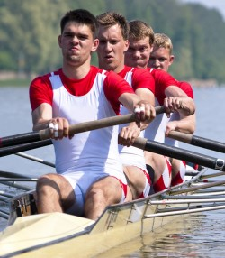 A coxed four during the start of a rowing regatta, with the second rower in full focus.